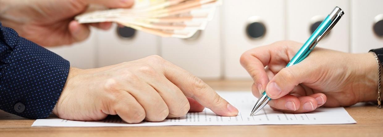Kredietverstrekker met geld in zijn hand wijst aan waar te tekenen op het papier